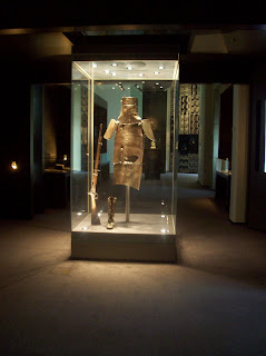 Ned Kelly's armor in a glass case lit by spotlights