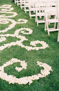A wedding aisle with a scrolled rose petal design.