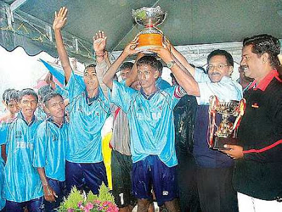 Winners: Mifa deputy president T. Mohan (right) looks on as Devamany (second from right) helps the Penang team lift the trophy.