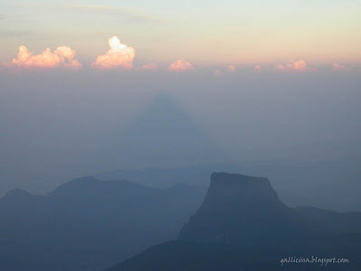 The sunrise from the summit of Adam's Peak showing the conical shadow of the Adam's Peak cast on the veil of mist on the western side for a brief moment