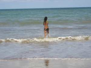 woman wading into small waves at the ocean