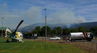 Fire-fighting helicopter at Huonville oval, having refuelled. Judds Creek Rd fire seen in background - 18 Feb 2007