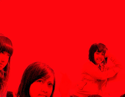 Three girls posing in the red background