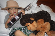 Mateo playing the guitar for his monkey!  He was wearing Aunt Mel's new hat!!