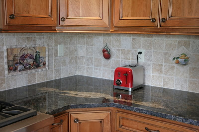 Tumbled marble backsplash reflected in a granite worktop The seemingly random pattern utilizes tumbled marble hung on the