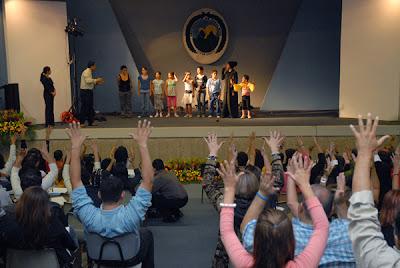Personas asistentes al congreso aplaudiendo después de una presentación de los niños del Centro Nacional Centeno Güell