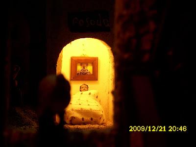 Curiosísimo detalle, mirando por la ventana de la posada del Belén de Clemen y Mª Sierra. En la pared se aprecia un cuadro con la imagen de Nuestra Patrona La Virgen de la Sierra