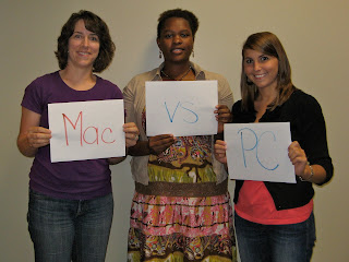 Marth Yim holding Mac sign Gina holding vs. and Ashley holding PC