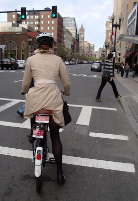 chic cyclist in a trench coat