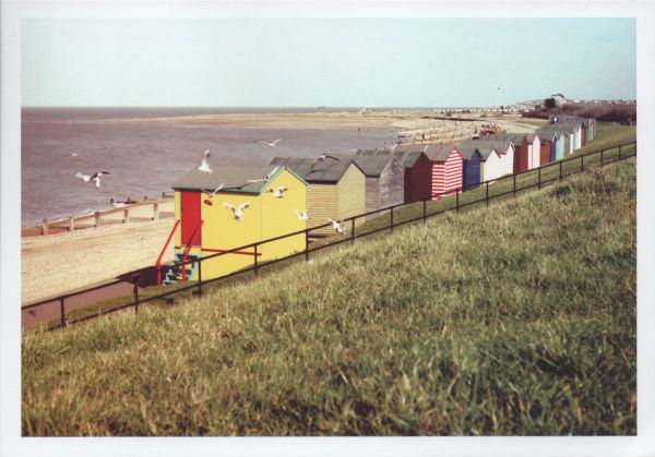 row of beach huts on shingle beach