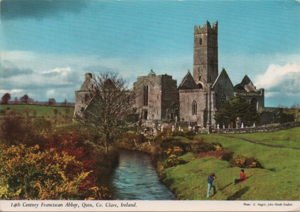 postcard showing the ruins of Quin Abbey, surrounded by a graveyard and fields, river nearby