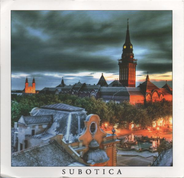 postcard showing Subotica town hall and city centre at dusk