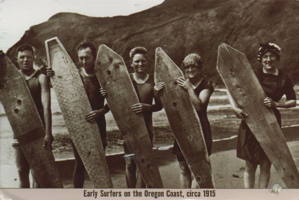 black and white postcard of surfers on the beach
