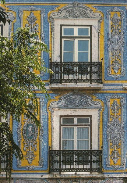blue and yellow tiles on a house in Lisbon