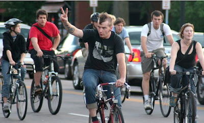 Bicyclist making peace sign to motorists