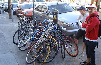 Image of bikes piled high on street, locked to one pole