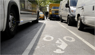 Image of bike lane in New York City, crowded by vans and buses