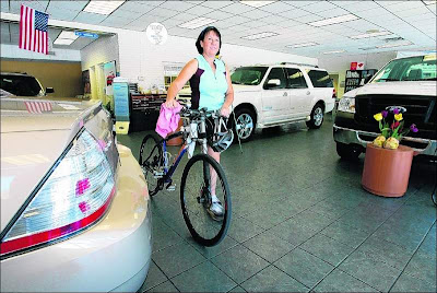 Peggy Strickland walks her bike through the showroom at the Lakeland Automall.