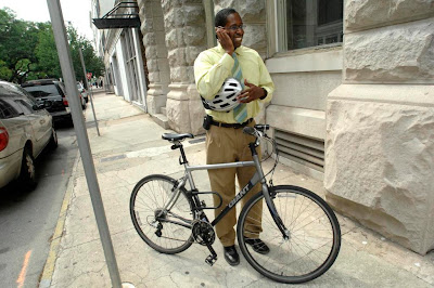Image of bicyclist taking a cell phone call, standing on the sidewalk next to his bike