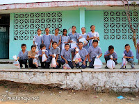 schoolchildren with their donated school supplies