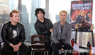 green day sitting at skysraper window with rock band poster behind