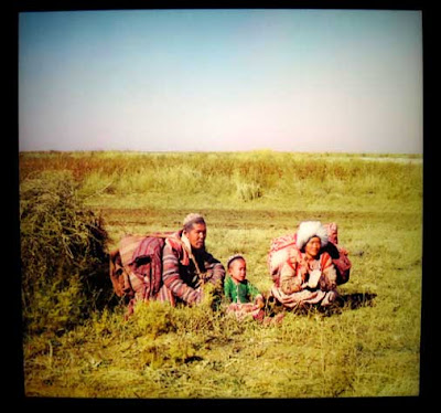 Nomadic man, woman and child sit in a field with their belongings