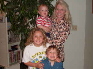 Photo of blond smiling woman with three children