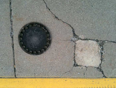 Round plastic hubcap near a square crack in a sidewalk, yellow curb at bottom