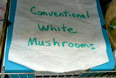Hand-written sign on box in produce section, White conventional mushrooms