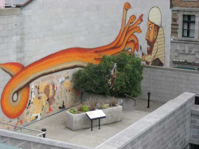 Large graffiti-like painting of a serpent in orange, over a small concrete planter with brown grasses visible