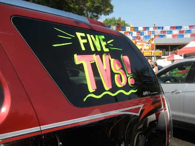 Back of an SUV painted with a sign that says FIVE TVs!