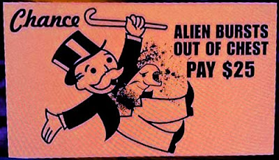 Orange Monopoly-type card with the Alien bursting out of the Uncle Moneybags' chest