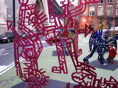 Kokopelli-like metal cut-out sculptures in a range of bright colors