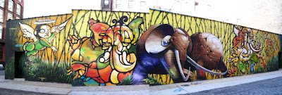 Wide painted mural of elephants in a range of style from manga to mechanistic