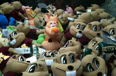 A single orange and white gingham Scooby Doo surrounded by a sea of Goldie Gopher dolls