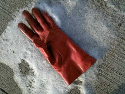 A single red leather glove lying in a patch of white snow on a sidewalk