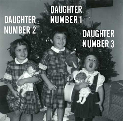 Black and white photo of three little girls in dresses in front of a Christmas tree. The smallest has her mouth wide open, while the older two are smiling
