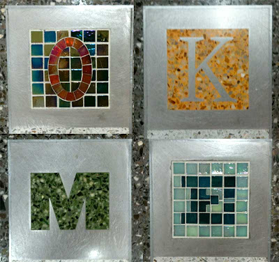 Closeups of the letters O K M and E in varying colors and materials