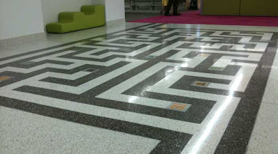 Black and white maze in a shiny floor with a green modernist couch in the background