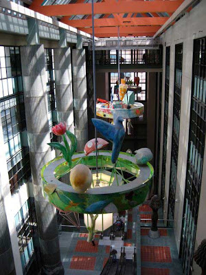 Colorful sculpture hanging high above an atrium that goes down five or six floors