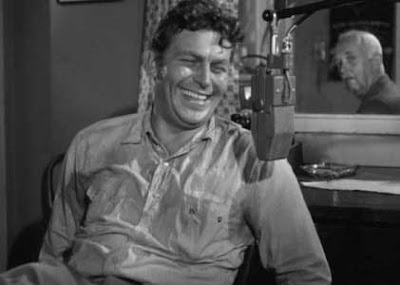 Andy Griffith as Lonesome Rhodes in front of a microphone
