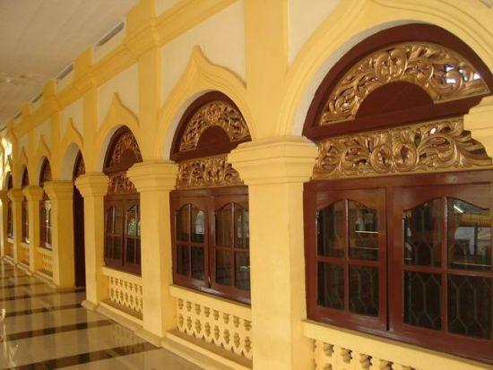 Dinding mesjid yang berbentuk unik dan jendela yang dibenuhi ukuran bermotif Melayu
