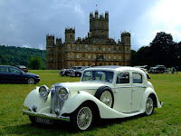 A lovely SS 100 Saloon in front of Highclere Castle
