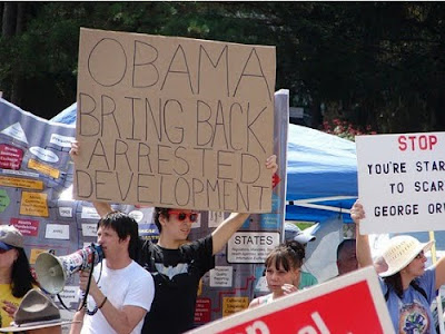 a hipster holding up a cardboard sign asking obama to bring back Arrested Development