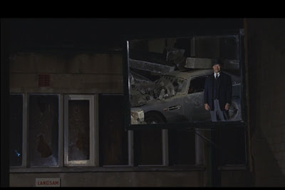 Bond thinks that a small mirror--more than 6 feet off the ground and off to the right--is a car heading towards him?