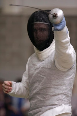 Jimmy Fruchterman in fencing gear, his face partially visible through the mask, holding his foil in front of him