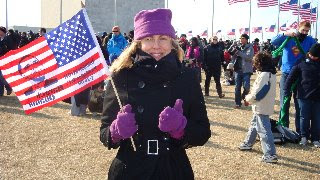 Ann in coat, purple hat, giving thumbs up sign and with flag