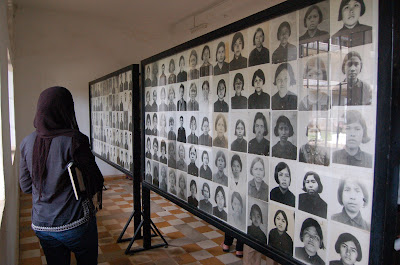 woman looking at wall of photographs of many individuals