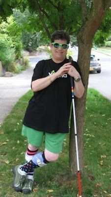 Liz Halperin with white cane, shades, and spectacular socks