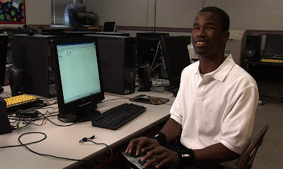 Steffon sitting at a computer, fingers on a Braille notetaker